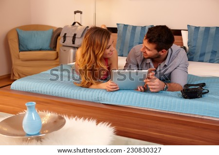 Happy young couple lying on bed in hotel room, using tablet pc. - stock photo