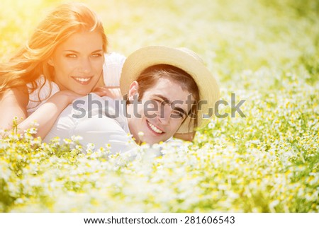 Happy, young couple lying on front in chamomile, daisy field.Copy space, lens flare - stock photo