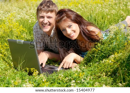 Happy young couple lying with a laptop on a wild meadow. - stock photo