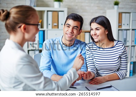 Happy young couple making deal with realtor - stock photo
