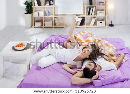Happy young couple making selfie in bed - stock photo