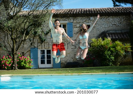 happy young couple man woman jumping in swimming-pool in summer vacations - stock photo