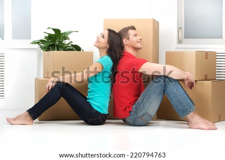 happy young couple moving in new home. man and woman sitting on floor back to back - stock photo