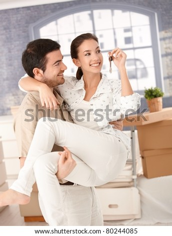 Happy young couple moving to new home, smiling, holding keys in hand.? - stock photo
