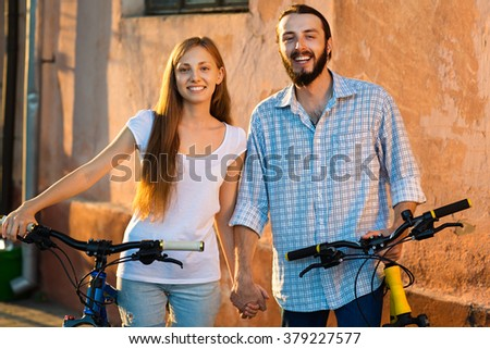 happy young couple of bicyclists talking in the street - stock photo