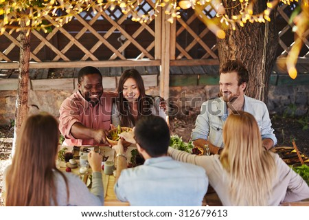 Happy young couple offering their friends traditional food by Thanksgiving table - stock photo