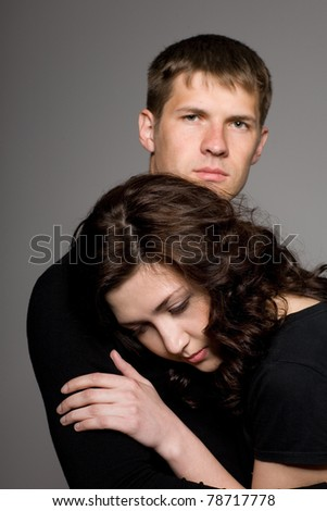 Happy young couple on a gray background. - stock photo