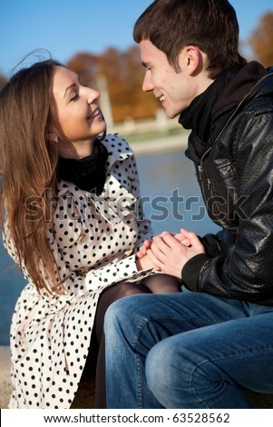Happy young couple outdoors at sunny autumn day - stock photo