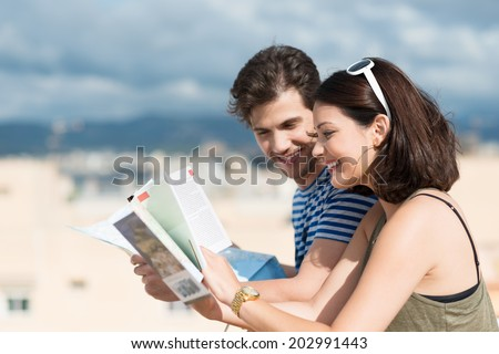 Happy young couple paging through tourist brochures as they stand close together on a hot tropical beach in the summer sunshine smiling as they look up information - stock photo