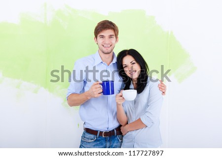 happy young couple paint in green color white wall of their new apartment home - stock photo