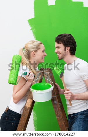 Happy young couple painting their new house bright green standing on a wooden stepladder smiling happily at each other as they hold a roller and paint brush - stock photo