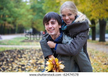 Happy young couple playing piggyback in the autumn park - stock photo