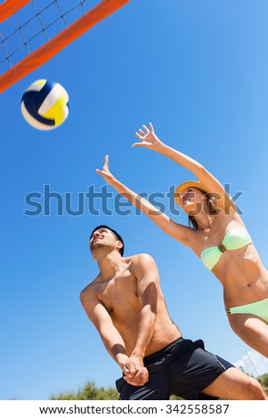 Happy young  couple playing volleyball on the beach - stock photo
