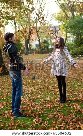 Happy young couple playing with leaves at fall - stock photo