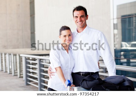 happy young couple pushing luggage trolley at airport - stock photo