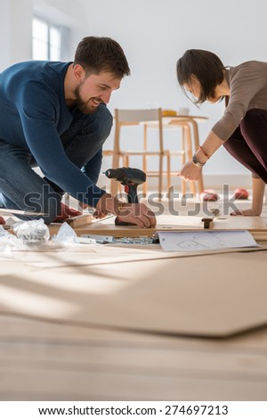 Happy young couple putting together self assembly furniture as they move into their new house. - stock photo