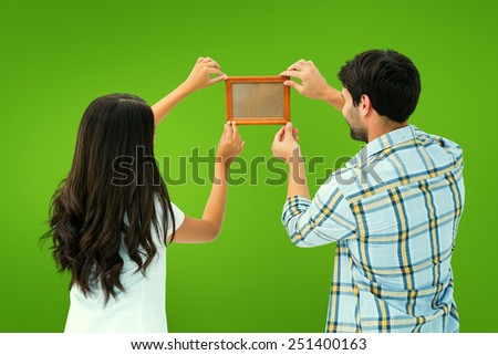 Happy young couple putting up picture frame against green vignette - stock photo