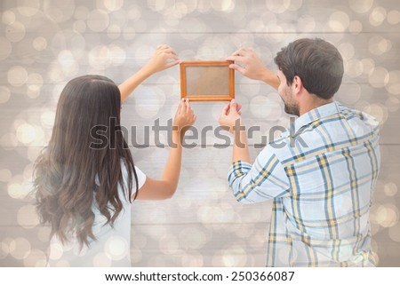 Happy young couple putting up picture frame against light glowing dots design pattern - stock photo