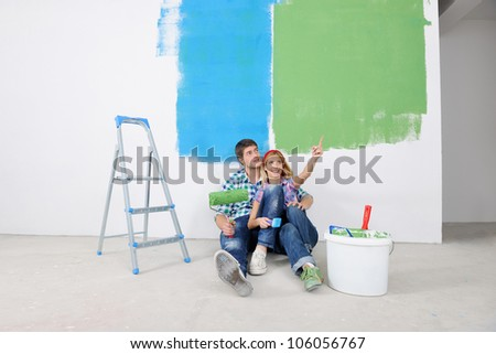 happy young couple relax after painting white wall in green and blue color in their new home - stock photo