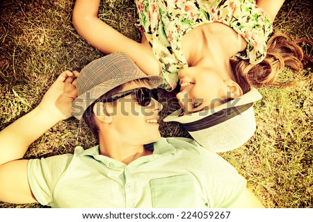 Happy young couple relaxing on the lawn in a summer park. Love concept. Vacation. - stock photo