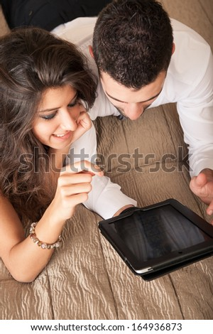 Happy young couple relaxing with tablet in hotel room. - stock photo