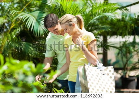 happy young couple shopping for plant in nursery greenhouse - stock photo