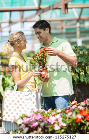 happy young couple shopping for plants in nursery - stock photo