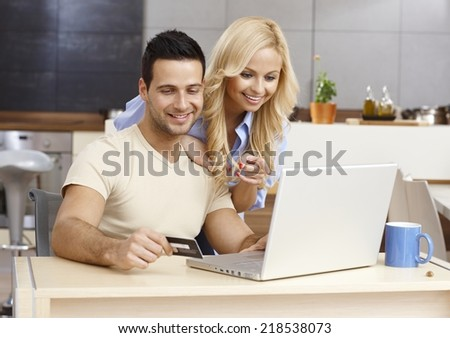 Happy young couple shopping online, using laptop computer and credit card, smiling. - stock photo
