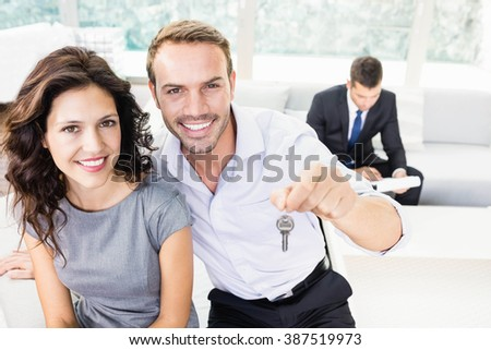 Happy young couple showing keys of their new house - stock photo