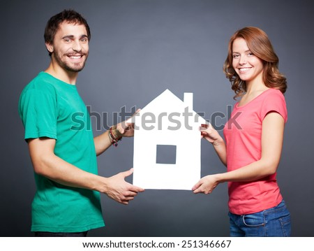 Happy young couple showing paper house - stock photo