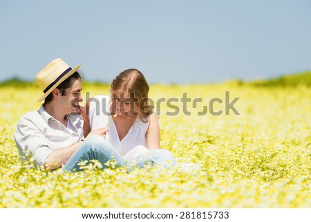 Happy, young couple sitting and enjoying outdoors at chamomile , daisy meadow.Copy space - stock photo