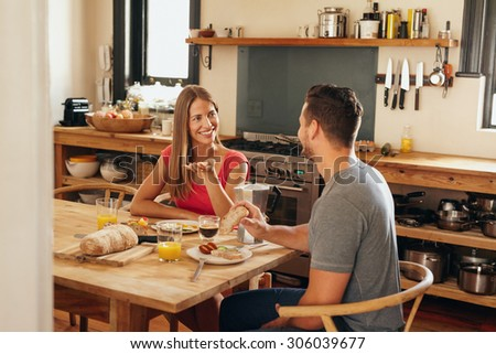Happy young couple sitting at breakfast table in morning having a conversation. Young woman talking with her boyfriend while eating breakfast together in kitchen. - stock photo