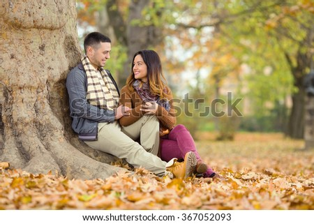 Happy young couple sitting beneath the tree in a park - stock photo