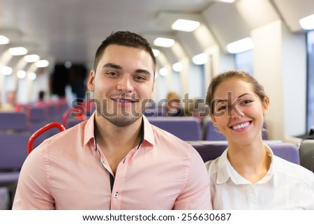 Happy young couple sitting in modern train. Focus on man - stock photo