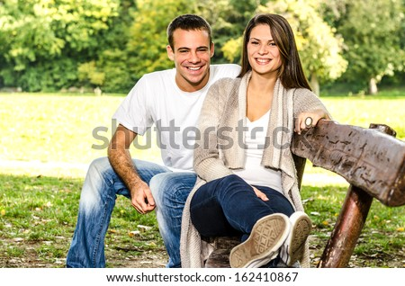 Happy young couple sitting on a bench and enjoying the autumn nature in the park - stock photo