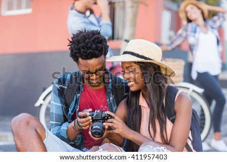 Happy young couple sitting on road looking in camera - stock photo