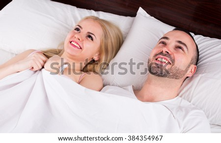 Happy young couple smiling in bed after having sex - stock photo