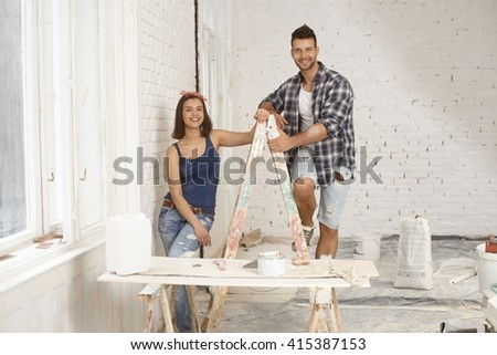 Happy young couple smiling, standing on ladder at home under construction. - stock photo