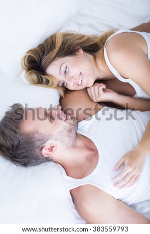 Happy young couple spending morning in bed - stock photo