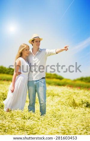 Happy, young couple standing in a chamomile, daisy field.Young man pointing hand - stock photo