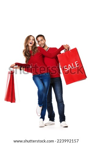 Happy young couple standing with a lot of shopping bags. Sale. Isolated over white. - stock photo