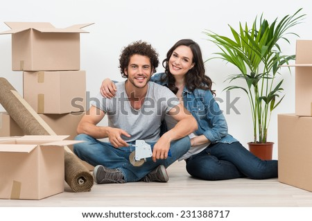 Happy Young Couple Surrounded With Cardboard Boxes At Home - stock photo