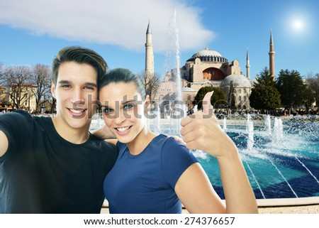 Happy, young couple taking a self portrait photo, selfie, in front of the Aya Sofia mosque in Istanbul ,Turkey - stock photo
