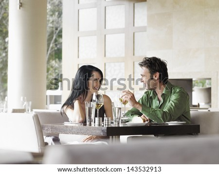 Happy young couple talking over wine at outdoor restaurant - stock photo