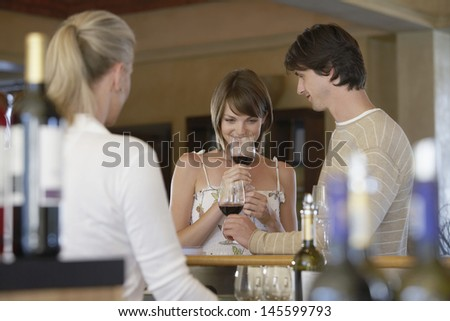 Happy young couple tasting wine with merchant in foreground - stock photo