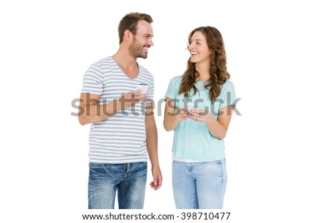 Happy young couple text messaging on mobile phone on white background - stock photo