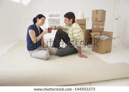 Happy young couple toasting coffee cups in new home - stock photo