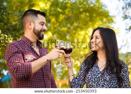 Happy young couple toasting with wine while having a picnic outdoors - stock photo