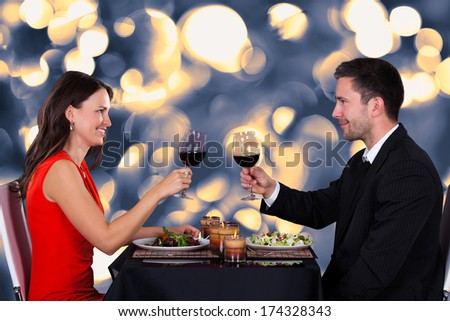 Happy Young Couple Tossing Wine In Restaurant - stock photo