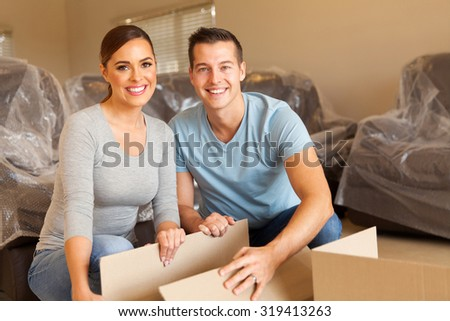 happy young couple unpacking boxes and moving into a new home - stock photo